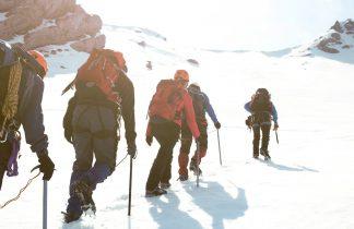 alpinistes gravissant une pente enneigée